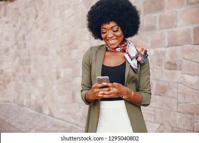 Fashionable girl in a summer city. Black lady in a green jacket. Woman in a red scarf. Famale with mobile phone