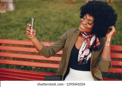 Fashionable girl in a summer city. Black lady in a green jacket. Woman in a red scarf. Girl sitting on a red bench. Famale with mobile phone