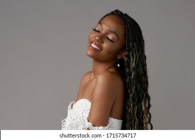 Fashionable girl wearing casual white top and blue jeans. Young african woman, Female model with long black african pigtails hair and perfect makeup. Studio shot at gray background