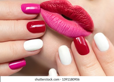 Fashionable glamorous manicure and lip makeup with red pink lipstick and multi-colored nail design with different shape.Nail art.