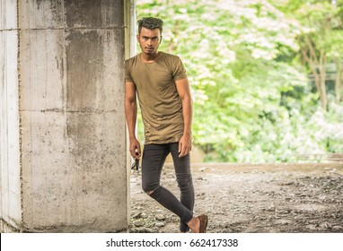Fashionable good looking trendy young male model with a gym fit body and muscles in an urbex urban concrete abandoned Industrial environment