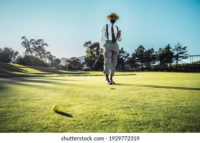 A fashionable good-looking mature bearded black guy in pants with suspenders and a straw hat, with a cigar and a golf club, is standing on the green grass of the lawn on a golf field on a warm evening