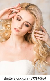 fashionable gown, beautiful blonde model, bride hairstyle and makeup concept - portrait of young pretty romantic lady in white festive wedding dress, slender woman indoors on light background