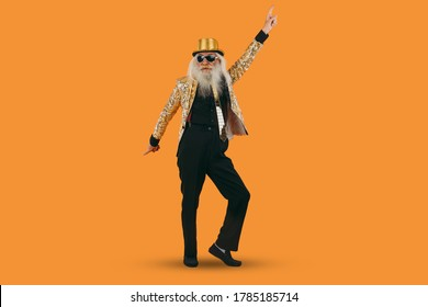 Fashionable grandfather posing with funny clothes. Senior man portraits on colored background