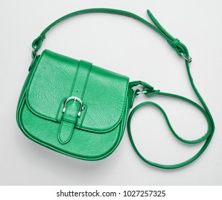 Fashionable green leather bag on a white background. Top view, women's accessories.