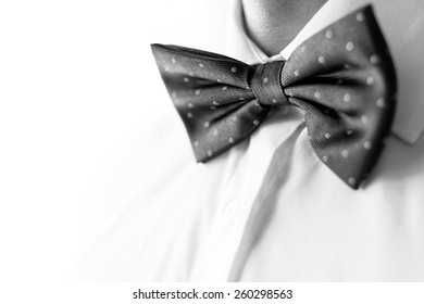 A fashionable groom wears a bowtie. A close-up shot of a man wearing a bowtie. B&W photo
