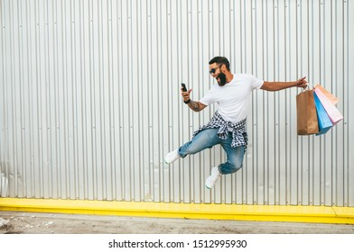 Fashionable guy with a beard runs in the air along an empty wall doing shopping in an online store, wearing blue jeans and holding blank craft paper bags. Discount, sale, season sales. Crazy emotions