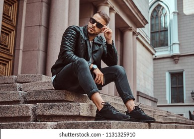 Fashionable guy dressed in a black jacket and jeans holds the smartphone sitting on steps against an old building in Europe.