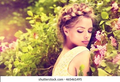 Fashionable hair disheveled braid around the head .Happy beautiful young model girl in summer blossom park.