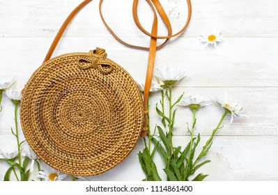 Fashionable handmade natural organic rattan bag and chamomile flowers on light background. Copy space, top view. Ecobags from Bali. Eco-bag concept.