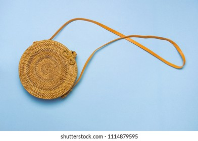 Fashionable handmade natural organic rattan bag on blue background flat lay. Copy space, top view. Ecobags from Bali. Eco-bag concept.