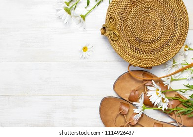 Fashionable handmade natural organic rattan bag, leather sandals, chamomile flowers on light wooden background. Copy space, top view. Ecobags from Bali. Eco-bag concept.