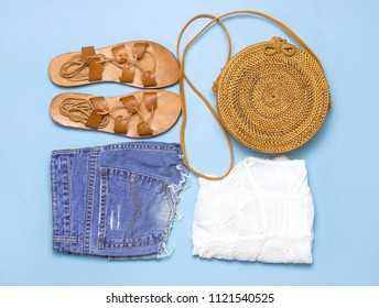 Fashionable handmade natural organic rattan bag, leather sandals, denim shorts, white blouse on blue background flat lay. Copy space, top view. Ecobags from Bali. Eco-bag concept.