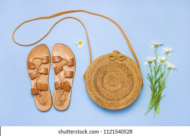 Fashionable handmade natural organic rattan bag, leather sandals, chamomile flowers on blue background flat lay. Copy space, top view. Ecobags from Bali. Eco-bag concept.
