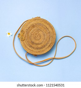 Fashionable handmade natural organic rattan bag and chamomile flowers on blue background flat lay. Copy space, top view. Ecobags from Bali. Eco-bag concept.