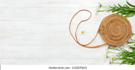Fashionable handmade natural organic rattan bag and chamomile flowers on light wooden background. Ladies bag made of natural material. Copy space, top view. Ecobags from Bali. Eco-bag concept.