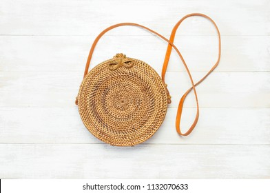 Fashionable handmade natural organic rattan bag on light wooden background. Ladies bag made of natural material. Copy space, top view. Ecobags from Bali. Eco-bag concept.