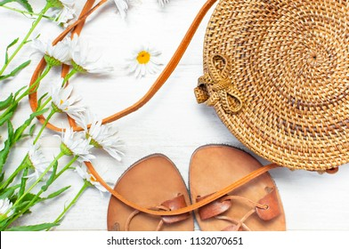 Fashionable handmade natural organic rattan bag, leather sandals, chamomile flowers on light wooden background. Ladies bag made of natural material. Copy space, top view. Ecobags from Bali. Eco-bag