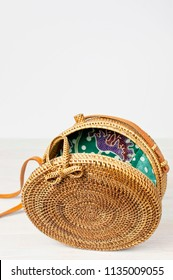 Fashionable handmade natural organic rattan bag on light wooden background. Ladies bag made of natural material. Ecobags from Bali. Eco-bag concept.