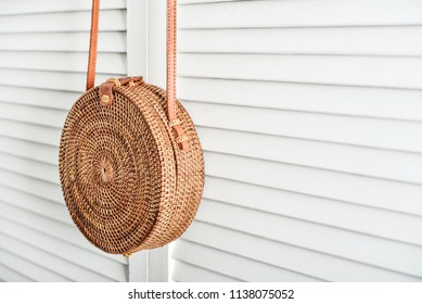 Fashionable handmade natural organic rattan bag  on white wooden background. Ecobags from Bali. Eco-bag concept.
