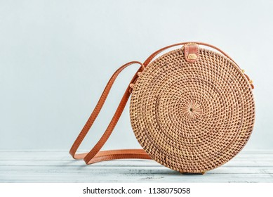 Fashionable handmade natural organic rattan bag on blue background closeup. Ecobags from Bali. Eco-bag concept.