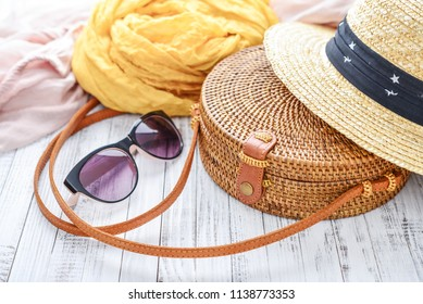 Fashionable handmade natural organic rattan bag with clothes and sunglasses on wooden background closeup. Ecobags from Bali. Eco-bag concept.