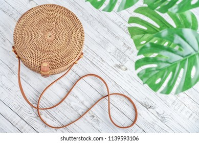 Fashionable handmade natural organic rattan bag  on white wooden background, top view. Ecobags from Bali. Eco-bag concept.