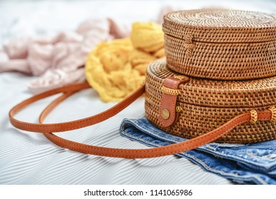 Fashionable handmade natural organic rattan bag with clothes on bed closeup. Ecobags from Bali. Eco-bag concept.