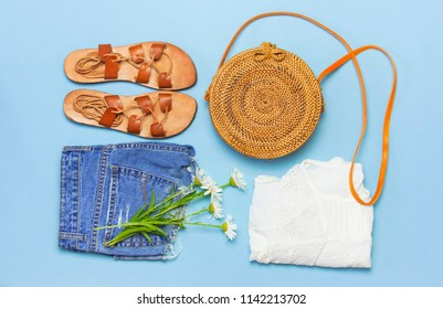 Fashionable handmade natural organic rattan bag, leather sandals, denim shorts, white blouse on blue background flat lay. Copy space, top view. Rattan handbag, ecobags from Bali. Eco-bag concept.