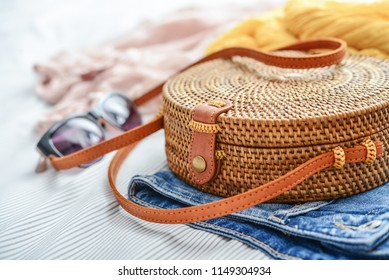 Fashionable handmade natural organic rattan bag with clothes and sunglasses on bed closeup. Ecobags from Bali. Eco-bag concept.
