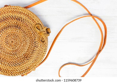 Fashionable handmade natural organic rattan bag on light wooden background. Ladies bag made of natural material. Copy space, top view. Trendy bamboo bag Ecobags from Bali.