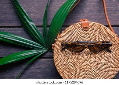 Fashionable handmade natural organic rattan bag with clothes and sunglasses.
