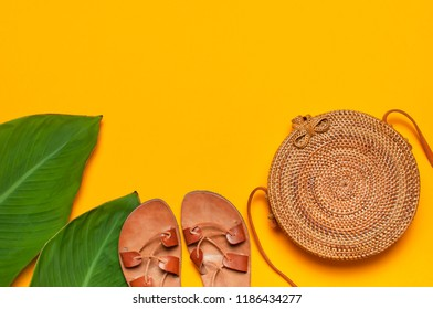 Fashionable handmade natural organic rattan bag, leather sandals, tropical leaves on bright yellow minimalistic background. Ladies bag made of natural material. Copy space, top view. Ecobags from Bali