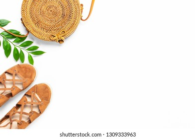 Fashionable handmade natural organic rattan bag, sandals, green twig on white background. Ladies bag Female fashion background. Flat lay, top view, copy space. Ecobags from Bali. Stylish rattan bag