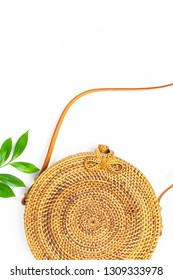 Fashionable handmade natural organic rattan bag and green twig on white background. Ladies bag made of natural material. Flat lay, top view, copy space. Ecobags from Bali. Stylish rattan bag