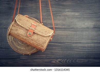 Fashionable handmade natural organic rattan bags on wooden background. Ecobags from Bali. Eco-bag concept.