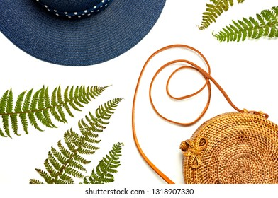 Fashionable handmade natural organic rattan bag, hat and green fern leaves, pink flower isolated on white background. Ladies bag, Stylish rattan bag. Flat lay, top view, copy space. Ecobags from Bali.