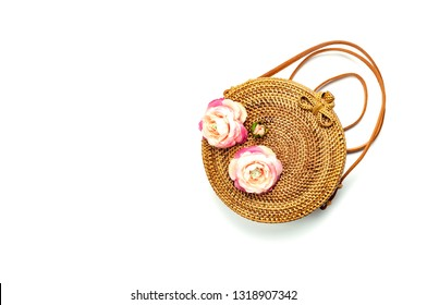 Fashionable handmade natural organic rattan bag and green fern leaves, pink flower isolated on white background. Ladies bag, Stylish rattan bag. Flat lay, top view, copy space. Ecobags from Bali.