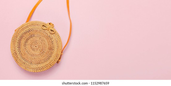 Fashionable handmade natural organic round rattan bag on pink background flat lay. Top view with copy space. Trendy bamboo bag Ecobags from Bali. Summer fashion concept.