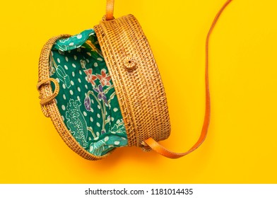 Fashionable handmade natural organic round rattan bag on bright yellow background flat lay. Top view with copy space. Trendy bamboo bag Ecobags from Bali. Summer fashion concept.