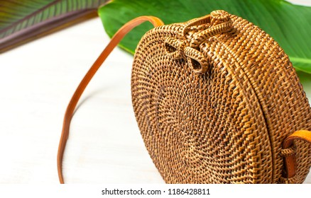 Fashionable handmade natural organic round rattan bag and tropical leaves on light wooden background flat lay with copy space. Trendy bamboo bag Ecobags from Bali. Summer fashion concept.