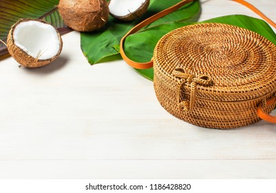 Fashionable handmade natural organic round rattan bag, fresh coconut and tropical leaves on light wooden background flat lay with copy space. Trendy bamboo bag Ecobags from Bali Summer fashion concept