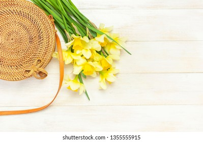 Fashionable handmade natural organic round rattan bag, yellow narcissus or daffodil flowers on light wooden background flat lay. Trendy bamboo bag Ecobags from Bali. Summer fashion concept Top view