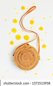 Fashionable handmade natural organic round rattan bag, yellow spring flowers on light gray background flat lay. Trendy bamboo bag Ecobags from Bali. Summer fashion concept Top view. Women's summer bag
