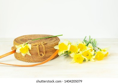 Fashionable handmade natural organic round rattan bag, yellow narcissus or daffodil flowers on light wooden background flat lay. Trendy bamboo bag Ecobags from Bali. Summer spring fashion concept