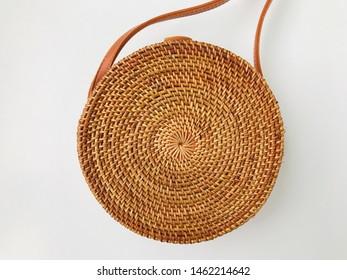 Fashionable handmade natural organic Round rattan bag: isolated straw Circle Balinese Crossbody Shoulder Bag on white background