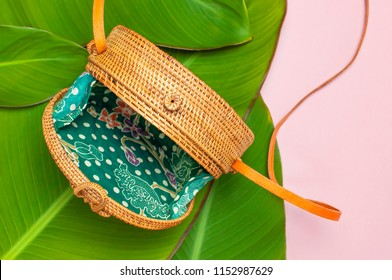 Fashionable handmade natural round rattan bag and tropical leaves on pink background flat lay. Top view with copy space. Trendy bamboo bag Ecobags from Bali. Summer fashion concept.