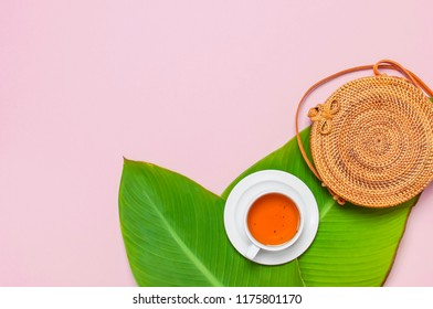 Fashionable handmade natural round rattan bag, cup of herbal tea and tropical leaves on pink background flat lay. Top view with copy space. Trendy bamboo bag Ecobags from Bali. Summer fashion concept