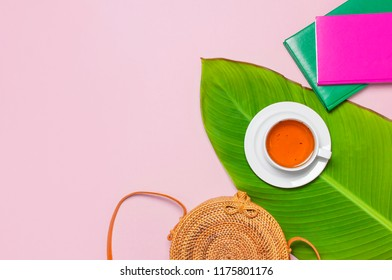Fashionable handmade natural round rattan bag, cup of herbal tea, colorful notepads and tropical leaves on pink background flat lay Top view. Trendy bamboo bag Ecobags from Bali Summer fashion concept