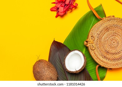 Fashionable handmade natural round rattan bag, fresh coconut and tropical leaves on bright yellow background flat lay. Top view Trendy bamboo bag Ecobags from Bali. Summer fashion concept.